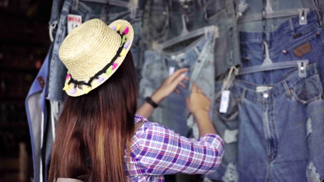 beautiful asian woman shopping on the chatuchak weekend market in the thailand vacation choosing choosing new clothes, looking through hangers with different casual colorful garments on hangers, shopping concept  for herself.business concept. - market stall stock videos & royalty-free footage