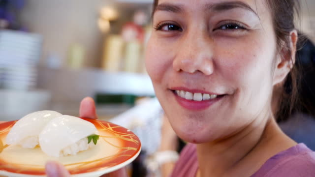 Beautiful Asian woman showing sushi in Sushi and Sashimi rolling on conveyer belt restaurant