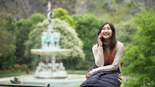 beautiful asian woman smiling talking and sitting in park - cambridge england stock videos and b-roll footage