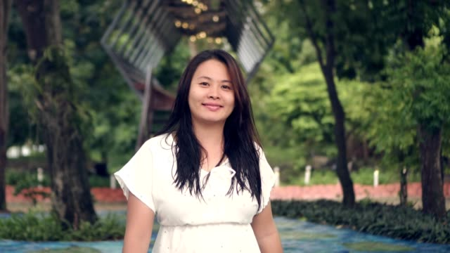 beautiful asian woman smiling walking green nature scene - medium shot stock videos & royalty-free footage