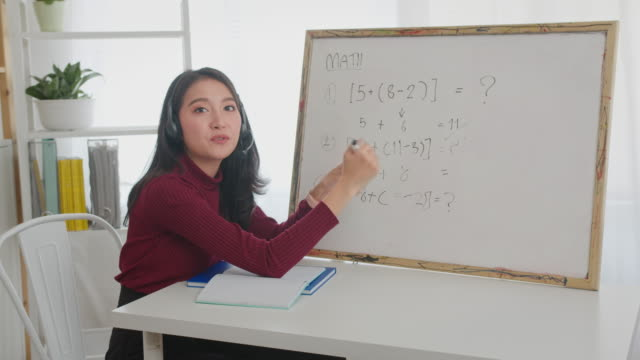 beautiful asian woman teaching mathematics online,smiling asian woman teacher speaking  doing math on video call or mathematics lesson class online for homeschooling. - tutorial stock videos & royalty-free footage