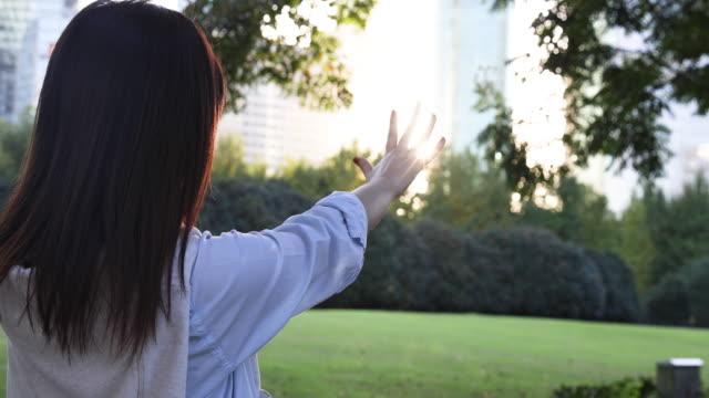 stockvideo's en b-roll-footage met 4k: mooie aziatische vrouw aanraken van zon flare op park, shanghai, china - 20 24 years