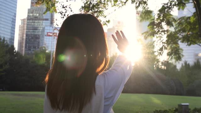 4K: schöne asiatische Frau unter Sonne Streulicht im Park, Shanghai, China