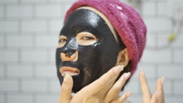 自宅の浴室で黒い保湿マスクを身に着けている美しいアジアの女性 - フェイスパック点の映像素材/bロール