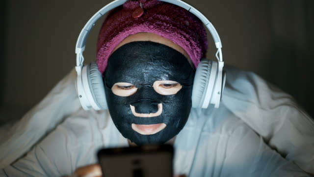 beautiful asian woman wearing a black moisturizing mask. - lying on front stock videos & royalty-free footage