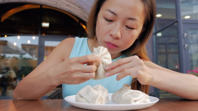 カフェでグルジアの肉料理を食べて食欲を持つ美しいアジアの女性 - ジョージア調点の映像素材/bロール