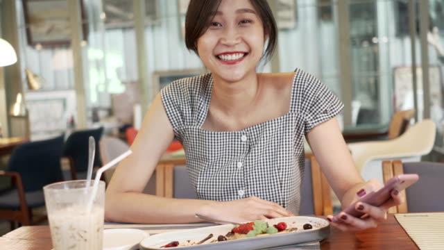 Vacker asiatisk kvinna med vackert leende njuta av att äta choklad kaka dessert i coffee shop och kul med Online Shopping på mobiltelefon