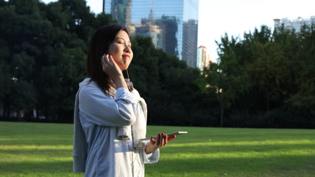 4K: Beautiful Asian woman with Digital Tablet at park,Shanghai,China