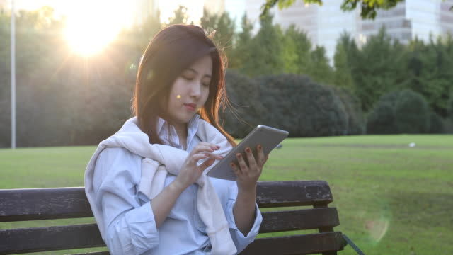 4k: beautiful asian woman with digital tablet at park,shanghai,china - east asian ethnicity video stock e b–roll