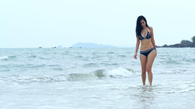 浜辺を歩く美しいアジアの若い女性。