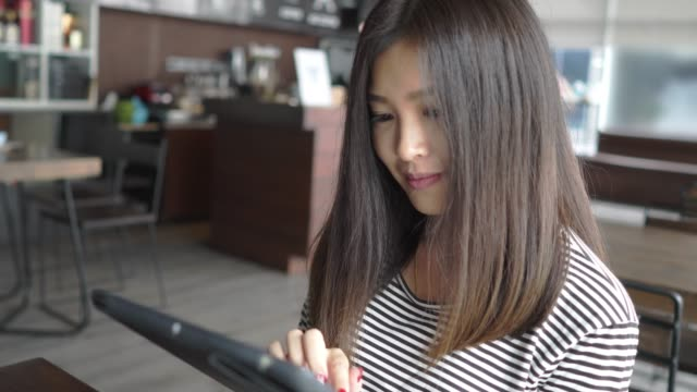 beautiful asian young woman working on tablet in coffee shop, close up - graphics tablet stock videos & royalty-free footage