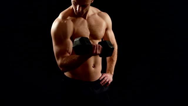 bella atleta si allena con un manubrio su uno sfondo nero - torso umano video stock e b–roll