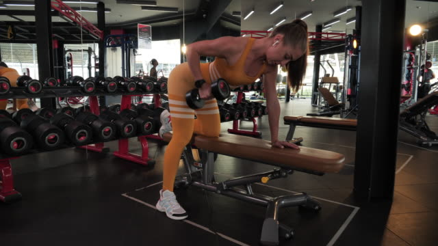 vídeos de stock, filmes e b-roll de a beautiful athletic young brunette woman in sportswear in the fitness room raises dumbbells. - self discipline