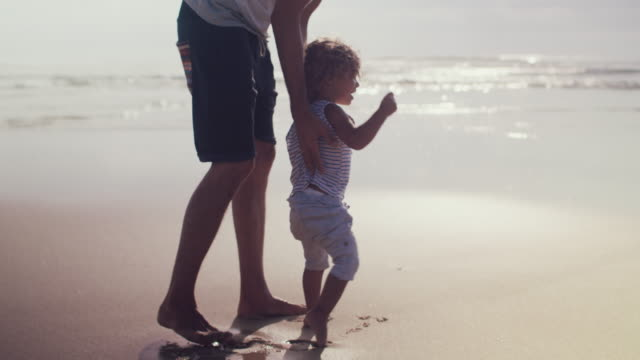 beautiful baby boy walking on beach with father - familie mit zwei generationen stock-videos und b-roll-filmmaterial
