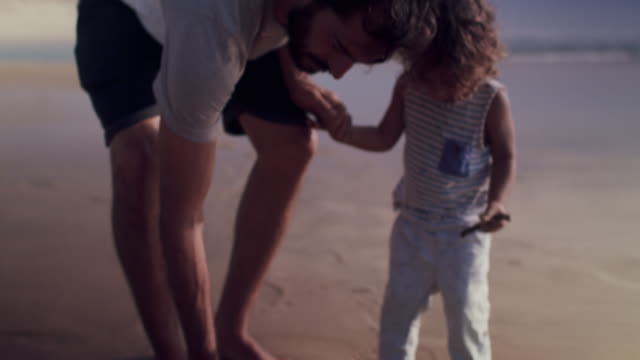 beautiful baby boy walking with father on beach - sohn stock-videos und b-roll-filmmaterial