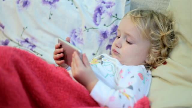 vídeos y material grabado en eventos de stock de hermosa niña con smartphone en la cama. - teléfono sin cable