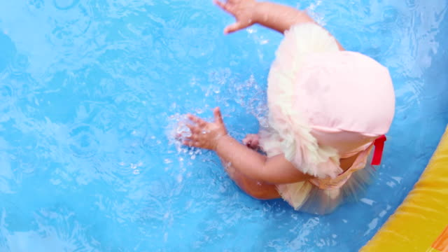 vidéos et rushes de beautiful baby playing and splashing and having fun in a splash pool by herself - pataugeoire
