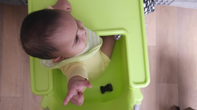 Beautiful baby sitting in her high chair having food and looking at the camera and pointing at it
