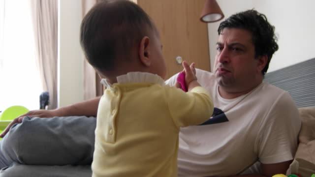 beautiful baby trying to play with her dad, he looks elsewhere - exhaustion stock videos & royalty-free footage
