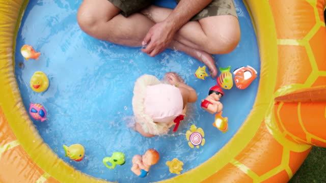 vídeos de stock, filmes e b-roll de beautiful baby with big eyes plays in a splash pool with her dad in the garden - animal de brinquedo