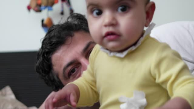 vídeos de stock, filmes e b-roll de beautiful baby with her dad suddenly runs towards the camera out of curiosity - vida de bebê