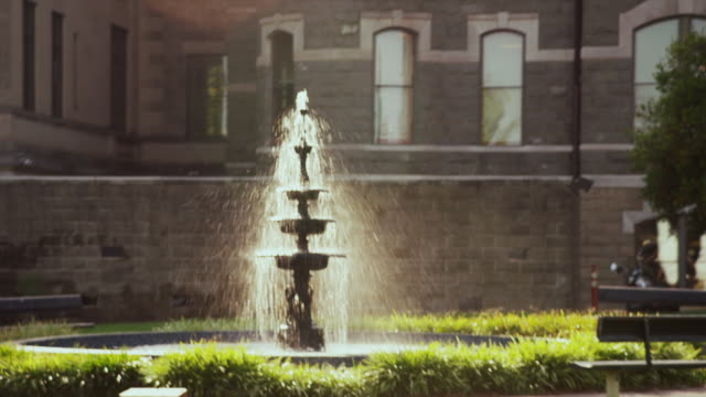 Beautiful backlit water fountain in the garden of an old stone civic building