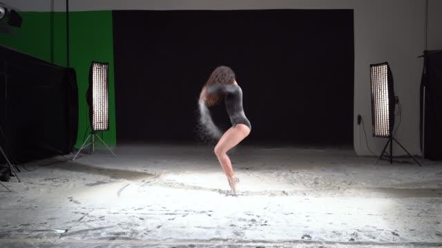 vídeos de stock, filmes e b-roll de linda bailarina dançando em uma pirueta com neve em pó no estúdio. câmera lenta - pirouette