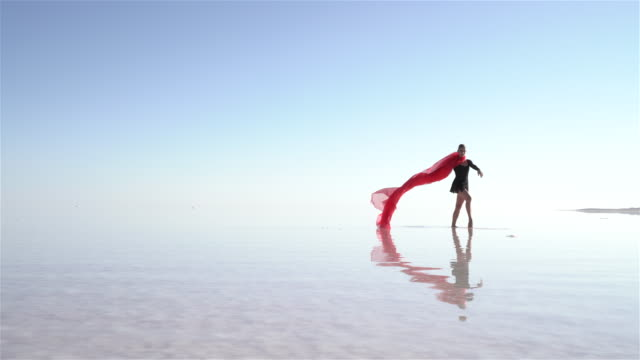 Beautiful ballerina dancing on the lake with red tulles