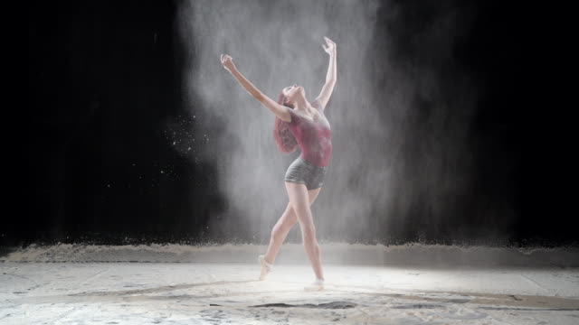 beautiful ballerina dancing with powder snow at studio. slow motion - pirouette stock videos and b-roll footage