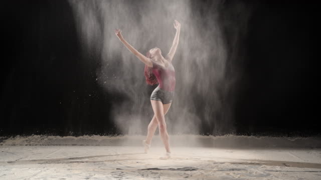 beautiful ballerina dancing with powder snow at studio. slow motion - ballet dancer stock videos & royalty-free footage
