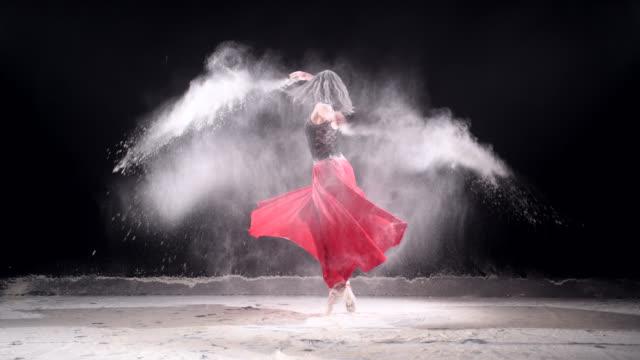Schöne Ballerina tanzen mit Pulverschnee im Studio.