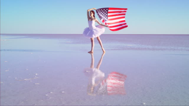Beautiful ballerina holding a American flag on the water. A windy day. Slow motion