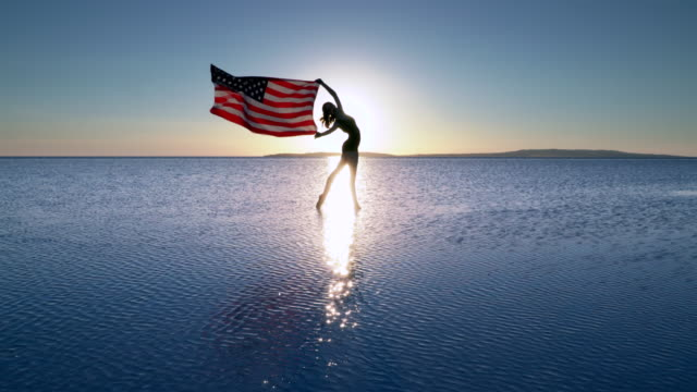 beautiful ballerina holding a american flag on the water. a windy day. slow motion - fourth of july stock videos and b-roll footage