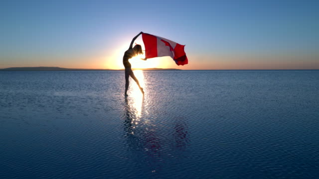 beautiful ballerina holding a canadian flag on the water. a windy day. - bandiera del canada video stock e b–roll