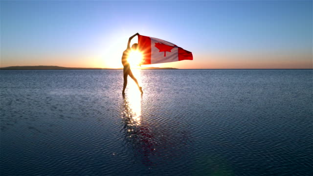 beautiful ballerina holding a canadian flag on the water. a windy day. slow motion - canadian flag stock videos & royalty-free footage