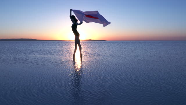 Beautiful ballerina holding a Japan flag on the water. A windy day. Slow motion