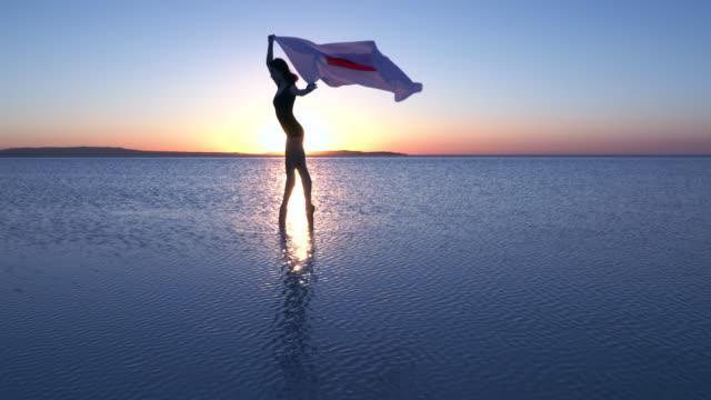 stockvideo's en b-roll-footage met prachtige ballerina houden een japanse vlag op het water. een winderige dag. slow motion - sunshine lake