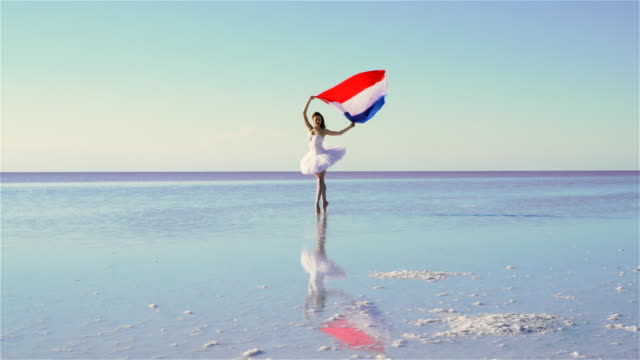 Beautiful ballerina holding a Netherland flag on the water. A windy day.