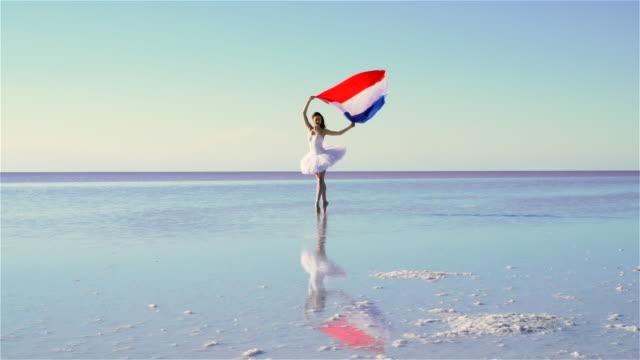 vídeos de stock, filmes e b-roll de linda bailarina segurando uma bandeira de netherland na água. um dia ventoso. - lago reflection