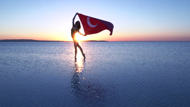 beautiful ballerina holding a turkish flag on the water. a windy day. - ballet dancer stock videos and b-roll footage