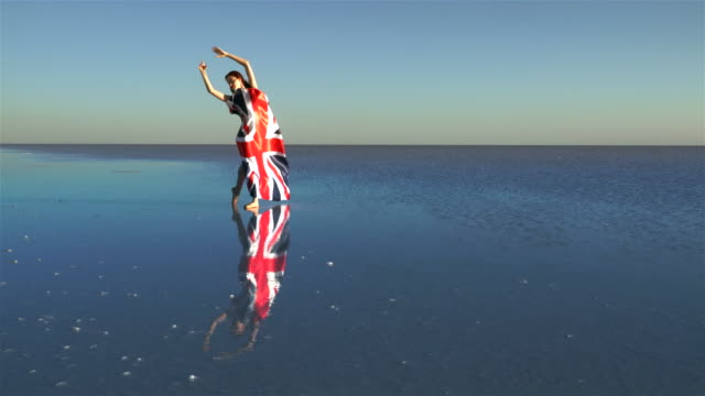 Beautiful ballerina holding a United Kingdom flag on the water. A windy day.