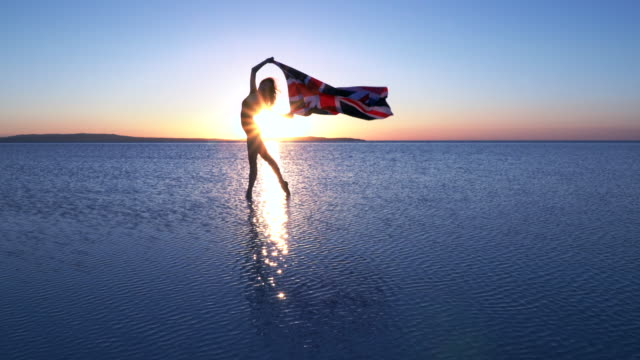 Beautiful ballerina holding a United Kingdom flag on the water. A windy day. Slow motion