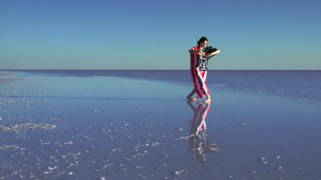Beautiful ballerina on the water with American Flag a windy day.