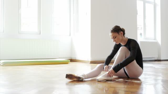 Beautiful ballerina tying her ballet shoes.