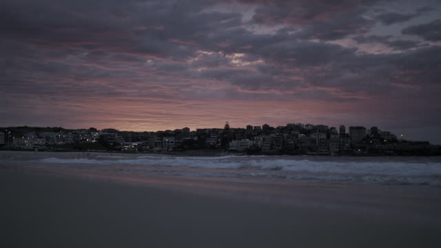 beautiful beach of modern city at dusk, bondi beach, australia - sunrise dawn stock videos & royalty-free footage