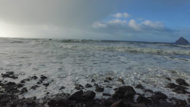beautiful beach with water crashing along rocky shoreline - fatcamera stock videos & royalty-free footage