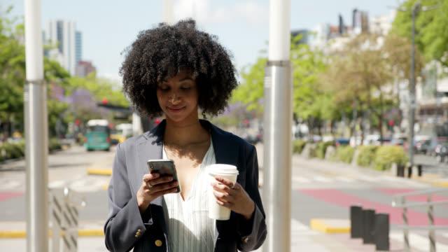schöne schwarze geschäftsfrau sms auf dem smartphone, während genießen sie einen take-out-kaffee nachdenklich aussehen - instant messaging stock-videos und b-roll-filmmaterial