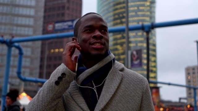 vídeos de stock, filmes e b-roll de empresário preto lindo casaco de inverno, ouvir música - negócios finanças e indústria