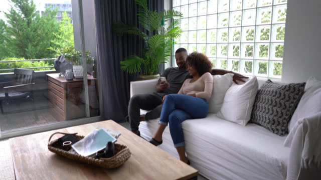 beautiful black couple at home relaxing watching something on smartphone laughing - zoom in stock videos & royalty-free footage