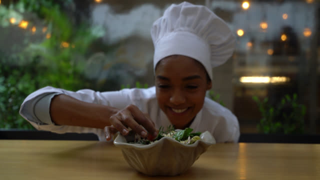 beautiful black female chef adding a finishing touch to a salad while facing camera smiling - chef stock videos & royalty-free footage